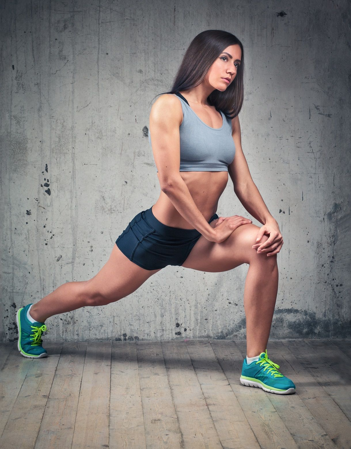 Sporty woman with muscular body doing fitness lunge on concrete wall background